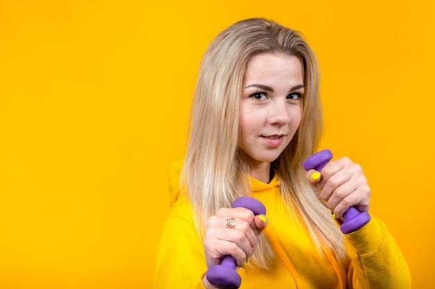 Portret van mooie jonge blonde vrouw in casual gele sportieve kleding die oefeningen met kleine paarse halters doet.