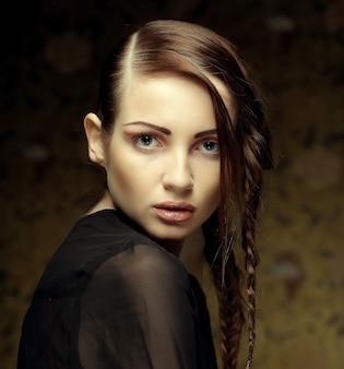 Portret van mooie jonge blonde vrouw met creatieve vlechten kapsel close-up