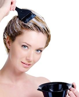 Portret van mooie jonge blonde vrouw met kom voor haarverf die haar hoofd kleuren dat op wit wordt geïsoleerd