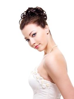 Portret van mooie jonge bruid met huwelijkskapsel - op witte achtergrond