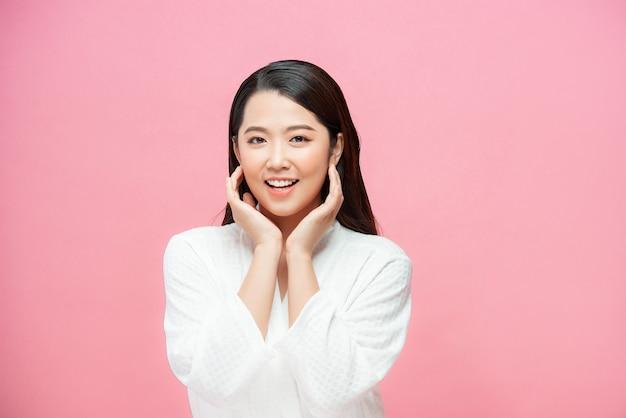 Portret van mooie jonge brunette met blote schouders die haar wangen aanraakt en naar de camera kijkt, op roze achtergrond