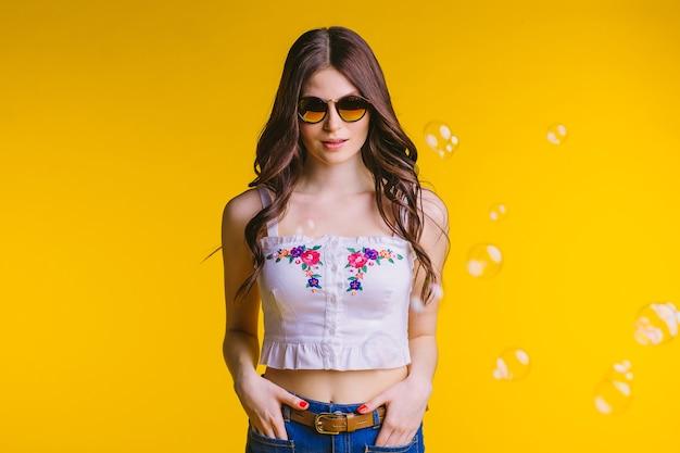 Portret van mooie jonge brunette met bril in witte top en spijkerbroek staande op een gele achtergrond in de studio.