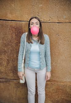 Portret van mooie jonge brunette tienermeisje die roze kauwgom blaast over een stenen muur achtergrond