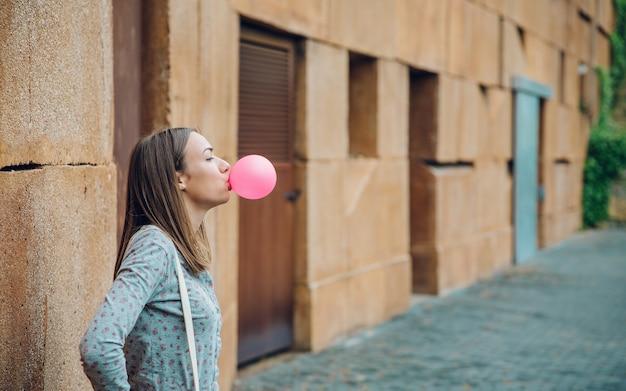 Portret van mooie jonge brunette tienermeisje die roze kauwgom blaast