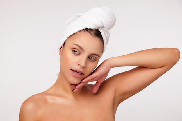 Portret van mooie jonge brunette vrouw met badhanddoek op haar hoofd opzij kijken en zachtjes haar gezicht aanraken, staande op witte achtergrond met blote schouders