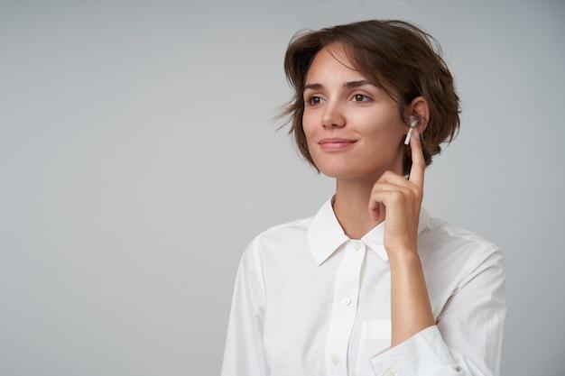 Portret van mooie jonge brunette vrouw met casual kapsel brillen dragen en wijsvinger erop houden, opzij kijken met zachte glimlach poseren in formele kleding