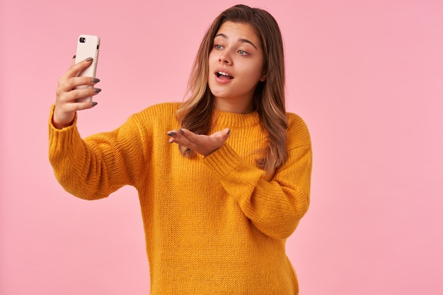 Portret van mooie jonge brunette vrouw met casual kapsel met verhoogde handpalm terwijl het hebben van videochat met haar smartphone, geïsoleerd op roze