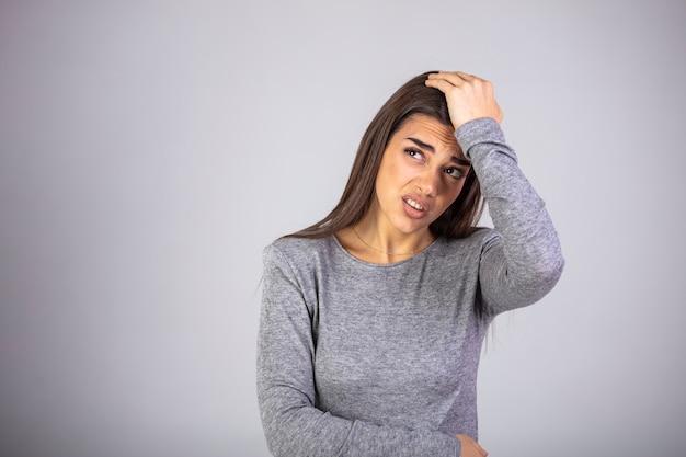 Portret van mooie jonge brunette wat betreft haar tempels gevoel stress, op een grijze achtergrond.