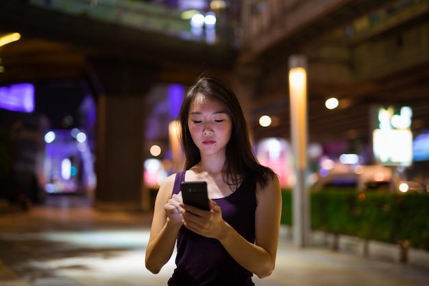 Portret van mooie jonge chinese vrouw buiten 's nachts
