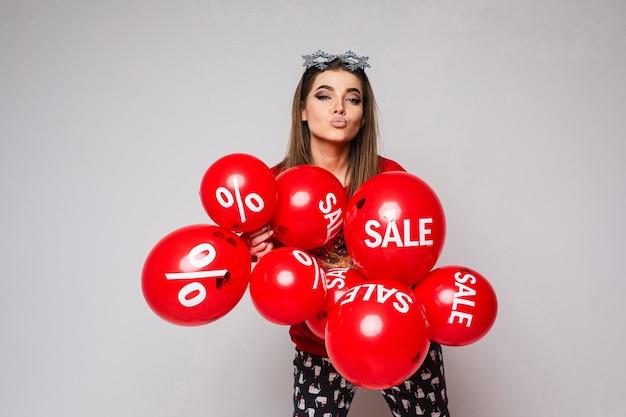 Portret van mooie jonge dame die een kus blaast en vele rode ballons houdt
