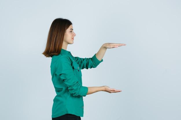 Portret van mooie jonge dame die groot grootteteken in groen overhemd toont en er zelfverzekerd uitziet