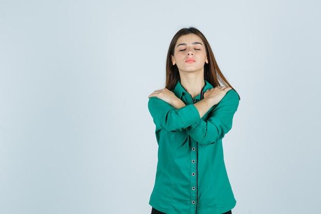 Portret van mooie jonge dame die handen op schouders houdt, ogen in groen overhemd sluit en ontspannen vooraanzicht kijkt