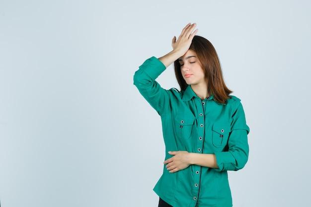 Portret van mooie jonge dame die hoofdpijn in groen overhemd voelt en moe vooraanzicht kijkt