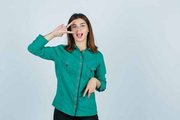 Portret van mooie jonge dame die v-teken dichtbij oog toont, tong in groen overhemd uitsteekt en blij vooraanzicht kijkt