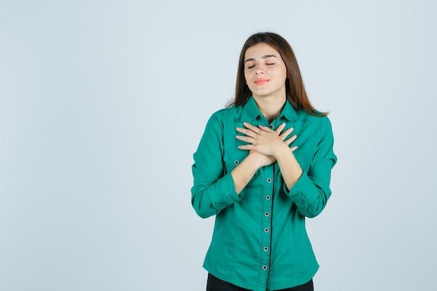 Portret van mooie jonge dame hand in hand op de borst in groen shirt en op zoek verrukt vooraanzicht