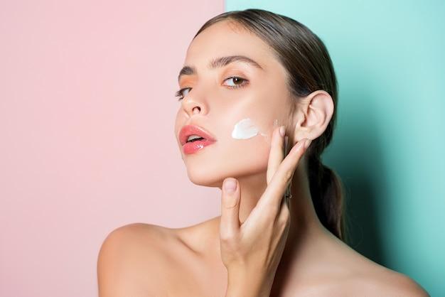 Portret van mooie jonge dame wang aan te raken met hand die gezichtscrème toepast.