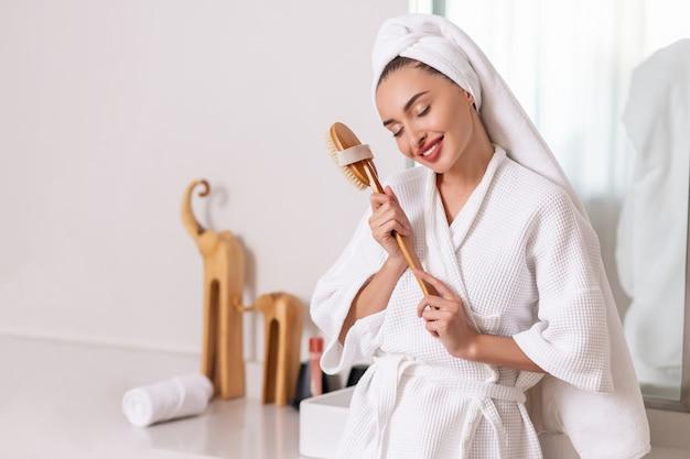 Portret van mooie jonge de massageborstel van de vrouwenholding