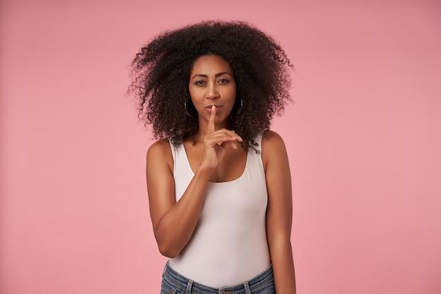 Portret van mooie jonge donkere dame met krullend haar die wijsvinger op haar lippen houdt, vraagt om geheim te houden, vrijetijdskleding draagt op roze