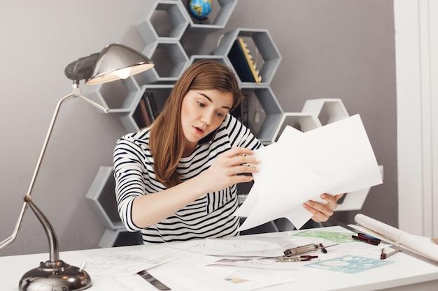 Portret van mooie jonge donkerharige geconcentreerde europese vrouwelijke freelance ontwerper praten aan de telefoon met teamleider, proberen om papieren te organiseren voor de vergadering van morgen.