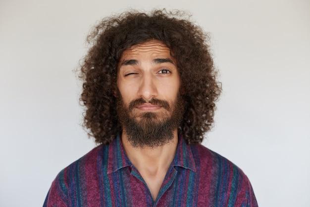 Portret van mooie jonge donkerharige man met krullende baard met gevouwen lippen oog gesloten houden tijdens het kijken, het dragen van vrijetijdskleding