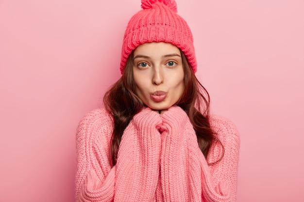 Portret van mooie jonge europese vrouw houdt lippen afgerond, handen onder de kin, kijkt direct naar de camera, draagt warme muts en trui, vormt op roze achtergrond.