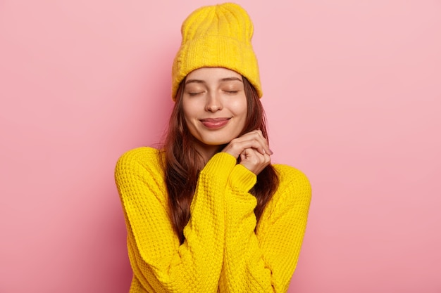 Portret van mooie jonge europese vrouw houdt ogen dicht, draagt levendige gele gebreide trui en hoofddeksels, geïsoleerd op roze achtergrond.