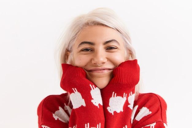 Portret van mooie jonge europese vrouw met bob rommelig kapsel en gezichtspiercing poseren bij lege witte muur in stijlvolle rode trui, kin op gestrekte mouwen plaatsen en glimlachen