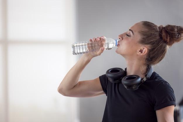 Portret van mooie jonge fit vrouw drinkwater tijdens traning in de sportschool.