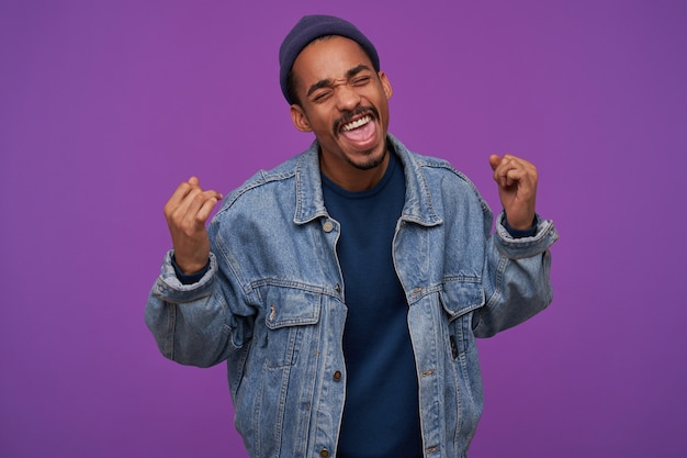 Portret van mooie jonge gelukkig donkere bebaarde brunette man ogen gesloten houden terwijl hij gelukkig zijn vuisten opheft, staande over paarse muur in vrijetijdskleding