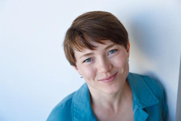 Portret van mooie jonge gelukkig lachende vrouw met kort haar in blauwe kleding,