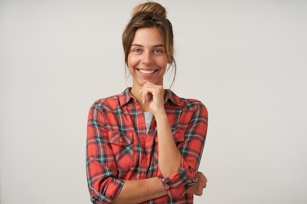 Portret van mooie jonge gelukkige vrouw met natuurlijke make-up houden opgeheven hand op haar kin en vrolijk lachend naar de camera terwijl poseren op witte achtergrond