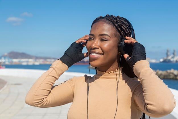 Portret van mooie jonge glimlachende afro-amerikaanse vrouw met hoofdtelefoons, met overzees en hemel, promenade.