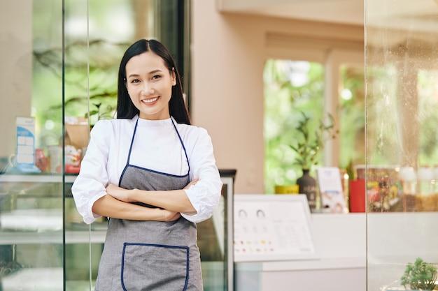 Portret van mooie jonge glimlachende kleine coffeeshopeigenaar die zich bij ingang bevindt