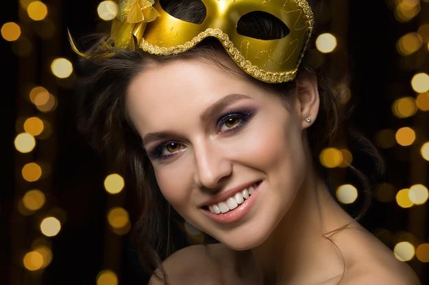 Portret van mooie jonge glimlachende vrouw die gouden partijmasker met gouden lichten draagt