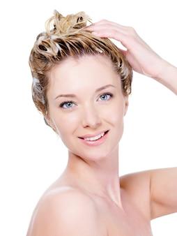 Portret van mooie jonge glimlachende vrouw die haar haar wast dat op wit wordt geïsoleerd