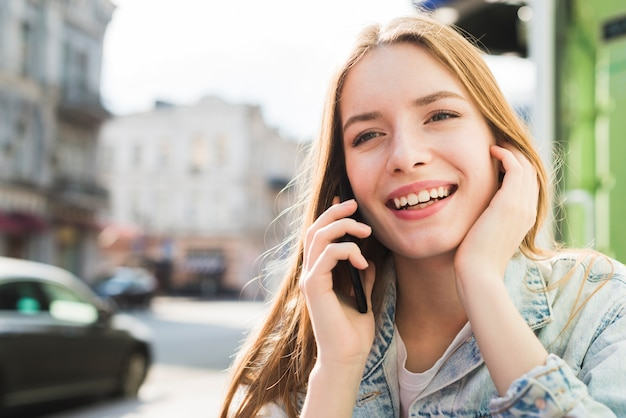 Portret van mooie jonge glimlachende vrouw die op cellphone spreekt