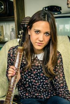 Portret van mooie jonge hipster meisje met akoestische gitaar zittend in een bank thuis. retro vintage kleuren editie