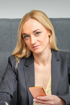 Portret van mooie jonge kaukasische onderneemster met smartphone die in bureau werkt
