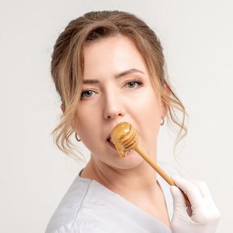 Portret van mooie jonge kaukasische vrouw die honing met houten lepel eet