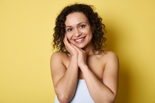 Portret van mooie jonge lachende afro-amerikaanse vrouw met kort krullend haar, camera kijken terwijl poseren over geel allemaal met kopie ruimte