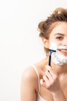 Portret van mooie jonge lachende blanke vrouw scheert gezicht met scheermes op witte achtergrond.