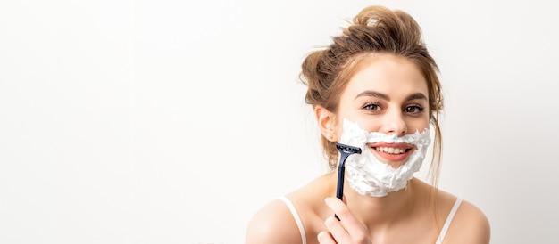 Portret van mooie jonge lachende blanke vrouw scheert gezicht met scheermes op witte achtergrond