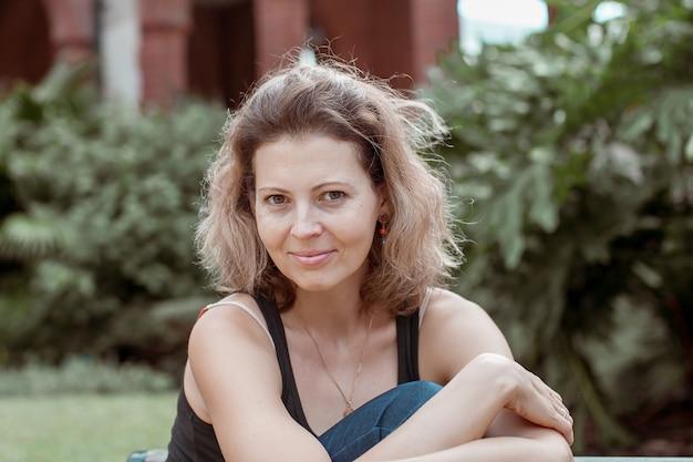 Portret van mooie jonge lachende vrouw buiten in het park.