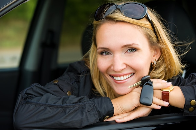 Portret van mooie jonge lachende vrouw in de nieuwe auto met sleutels - buitenshuis