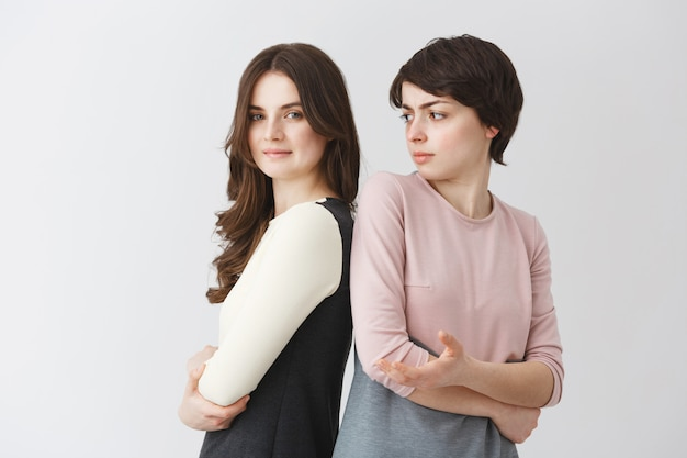 Portret van mooie jonge lesbische student meisje met lang haar poseren met kortharige kaukasische vriendin in bijpassende outfits. relatie concept.