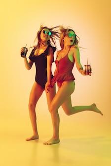 Portret van mooie jonge meisjes geïsoleerd op gele studio achtergrond in neonlicht. vrouwen in modieuze bodysuits. gezichtsuitdrukking, zomer, weekend, schoonheid, resortconcept. vakantie, jeugd.