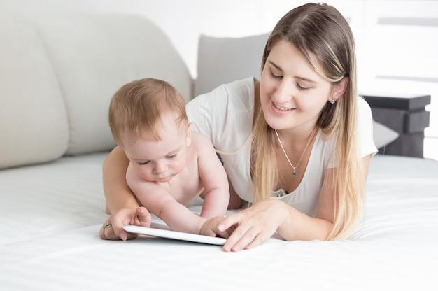 Portret van mooie jonge moeder die haar babyjongen leert tabletcomputer