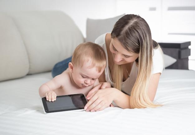 Portret van mooie jonge moeder die met haar baby op bed ligt en tablet gebruikt