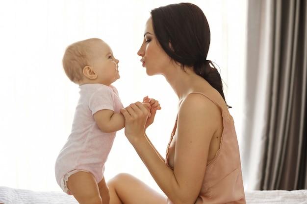 Portret van mooie jonge moeder in nachtkleding en haar baby kijken naar elkaar zitten in bed window oppervlak.