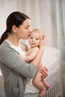 Portret van mooie jonge moeder meisje kuste haar pasgeboren baby close-up.